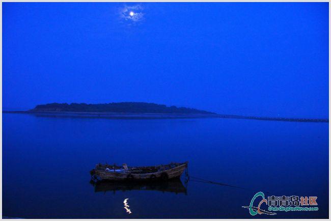 夜色中的海湾,一片宁静:月亮高高挂在天空,一只小船停泊在海岸边
